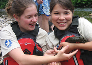 Photo of two female students holding a hellbender salamander.
