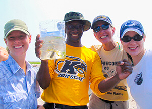 Photo of three students and teacher holding a plastic bag holding fish and underwater grasses.